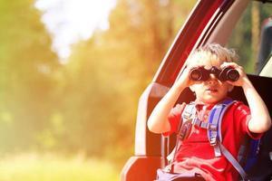 kleiner Junge, der durch Ferngläser schaut, fährt mit dem Auto