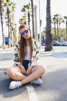 glamouröse junge Skateboarderin, die sich nach dem Fahren auf Penny Board entspannt foto