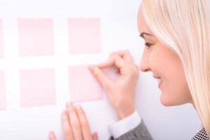 angenehme Geschäftsfrau, die mit Aufklebern arbeitet foto