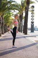 Sportlerin mit perfekter Figur, die Fitnessübung im Palmenpark tut foto