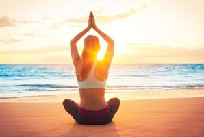 Yoga-Frau bei Sonnenuntergang foto