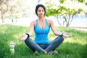 Frau meditiert über das grüne Gras foto