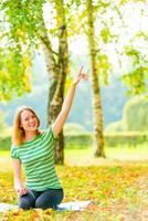 Mädchen mit dem schönen Lächeln, das im Park sitzt foto