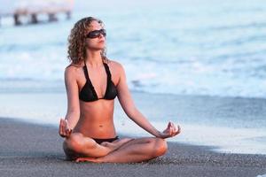 Körper des schönen Mädchens in der Meditation am Strand. Lotus Position foto