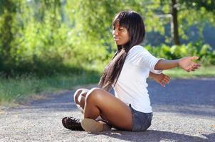 schöne ethnische Frau, die an einem Park meditiert foto