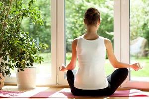 Frau macht Yoga zu Hause foto