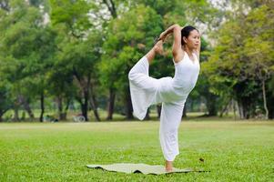 schöne Frau, die Yoga im Park praktiziert