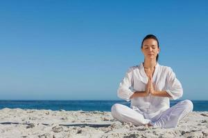 friedliche Frau, die Yoga am Strand praktiziert foto