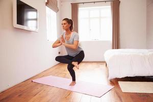 Frau, die Yoga-Fitnessübungen auf Matte im Schlafzimmer macht foto