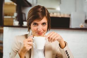 hübsche Geschäftsfrau, die ihren Kaffee genießt foto