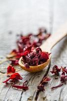 trockener Hibiskus-Tee im Holzlöffel foto