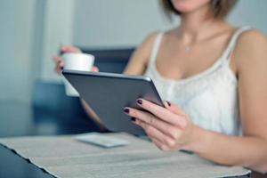 Frau genießt ein digitales Tablet foto