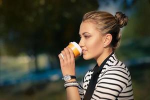 Frau trinkt heißes Getränk, das Natur genießt