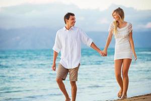 Paar genießt Sonnenuntergang am Strand