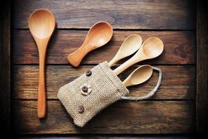 Holzlöffel in kleiner Tasche auf Holzhintergrund dunkelbraun. foto