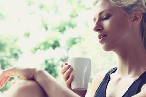 hübsche Frau, die ihren Morgenkaffee genießt foto