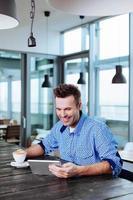 junger Mann, der eine Tasse Kaffee genießt foto