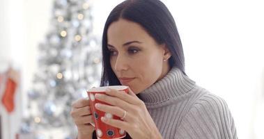 Frau genießt eine Tasse Weihnachtskaffee foto