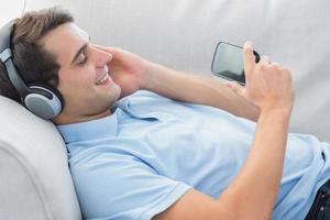 fröhlicher Mann, der Musik mit seinem Smartphone genießt