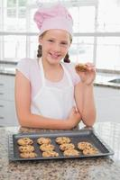 lächelndes junges Mädchen, das Kekse in der Küche genießt foto