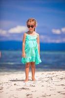 Porträt des kleinen glücklichen Mädchens, das Strandurlaub genießt foto