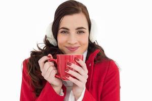 Frau in Winterkleidung genießt ein heißes Getränk