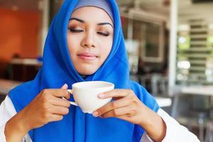 asiatische muslimische Frau, die eine Tasse Tee genießt foto