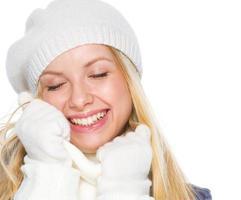 lächelndes Mädchen in der Winterkleidung, die weichen Schal genießt foto