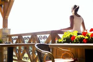 schöne Frau, die die Aussicht von der Terrasse genießt foto