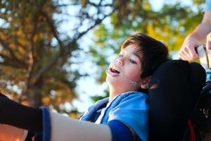 hübscher kleiner behinderter Junge im Rollstuhl, Sonnenuntergang im Freien genießend foto