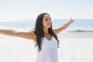 glückliche Brünette im weißen Sonnenkleid, das die Sonne genießt foto