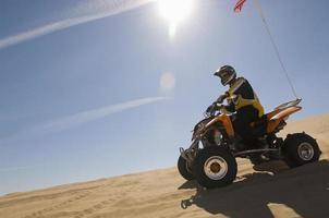 Mann, der Quadbike in der Wüste reitet