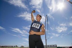männlicher Athlet, der sich darauf vorbereitet, Kugelstoßenball zu werfen (Linseneffekt)