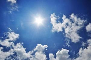 Sunburst und blauer Himmel Hintergrund mit flauschigen Wolken. foto