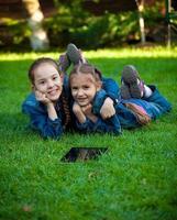 zwei Mädchen, die Spaß auf Gras mit Tablette haben
