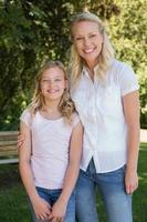 Mutter mit Arm um Tochter im Park stehend foto
