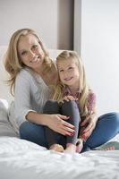 Porträt der glücklichen Mutter und der Tochter, die auf Bett sitzen