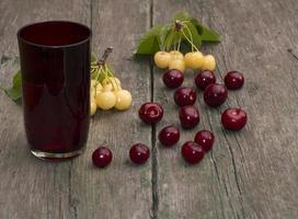 Glas Saft und Beere auf einem Holztisch foto