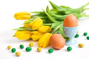 Strauß gelber Tulpen und Eier foto