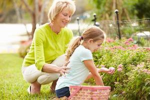 Großmutter mit Enkelin auf Ostereiersuche im Garten