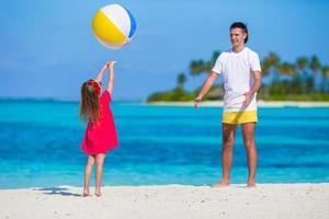 glücklicher Vater und Tochter spielen mit Ball am Strand
