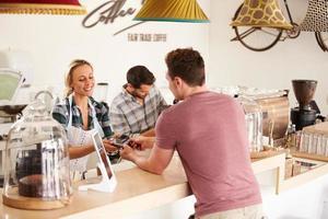 junger Mann, der für seine Bestellung in einem Café bezahlt