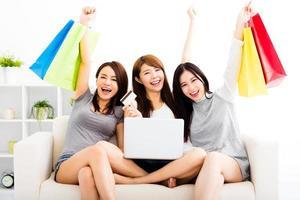 junge Frauen, die Laptop mit Online-Einkaufskonzept beobachten foto