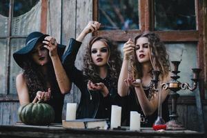 Drei alte Hexen führen ein magisches Ritual durch foto
