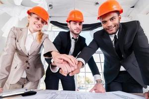 Architekten legten Hände auf Hände. Drei Geschäftsleute Architekt trafen sich foto