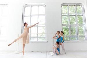 Drei kleine Ballerinas tanzen mit einem persönlichen Ballettlehrer im Tanz