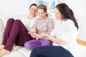 zwei Frauen und Mädchen mit digitalem Tablet foto