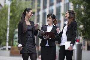 Drei Geschäftsfrauen unterhalten sich im Freien. foto