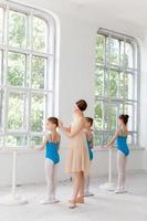 Drei kleine Ballerinas tanzen mit einem persönlichen Ballettlehrer im Tanz foto