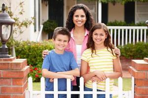 Mutter und Kinder außerhalb des Hauses foto